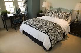 a small bedroom featuring a gilded black and white bed set dark aquamarine wall shading bedroom white bed set