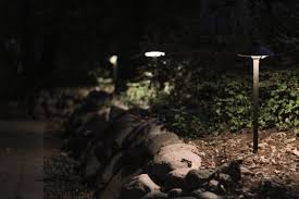 path lights installed in an elevated flower bed illuminate natural stone wall and walkway below area lighting flower bed