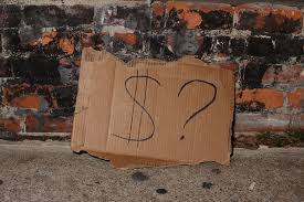 cardboard beggars sign with dollar symbol and question mark