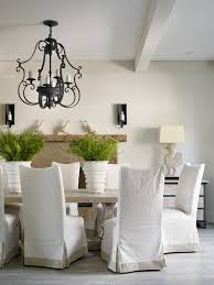 dining table parson chairs interior: parson chair slipcover dining room transitional with animal decor bird black iron chandelier exposed beam light