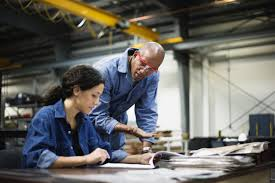 inspiring leadership characteristics female manager and male worker talking at desk in factory
