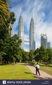 a man walking to work through klcc park petronas twin towers a man walking to work through klcc park petronas twin towers kuala lumpur