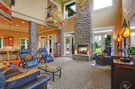 Luxury House Open Floor Plan  Spacious Living Room With High    Stock Photo   Luxury house open floor plan  Spacious living room   high ceiling  brick columns and fireplace  Furnished   leather furniture