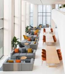a strip of blonde wood meeting tables separates the lounge areas sofas from an exhibition space architect office supplies