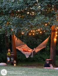 is there anything more soothing than a hammock gently swinging under string lights this easy to pull off setup is guaranteed to be your favorite spot to backyard string lighting ideas