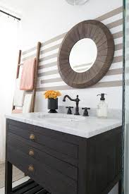 washstand bathroom pine: a beige striped bathroom wall is fitted with a round salvaged wood vanity mirror mounted above a black pine washstand adorning distressed brass cup pulls