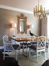white and taupe dining room features a jonathan adler meurice chandelier illuminating a stainless steel and calabria stainless steel