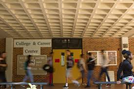 high school counselors help students a path to college or students walking by the college career center in between periods at lanier high school in