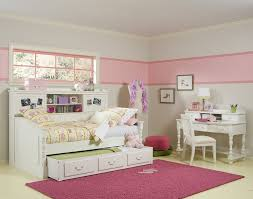 finest girl bedroom design featuring white finish wooden single bed with trundle and dark pink rugs and wooden study desk in white finishing be equipped biege study twin kids study room