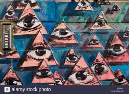Wall of a block of <b>flats painted</b> with triangles containing open eyes ...