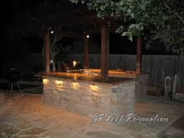 gallery outdoor kitchen lighting: stone wall and lighting for outdoor kitchen
