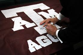 u s department of defense photo essay secretary of defense robert m gates autographs a texas a m flag during a to