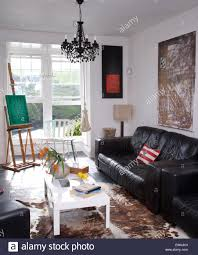 Of Living Rooms With Black Leather Furniture Black Leather Sofa And A White Coffee Table In Artists Living