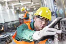 trade protectionism definition pros cons methods focused worker examining steel part in factory
