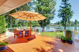 Outdoor Deck Design Ideas wood deck with beautiful lake view and outdoor patio furniture with umbrella
