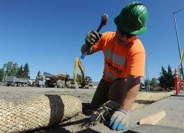 rundown stretch of spenard road in anchorage headed for major face shawn rice places erosion control straw along the sidewalk as earthwork ramps up on a