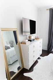 chic bedroom features a flatscreen tv atop a white ikea malm dresser adorned with gold ring hardware next to a gold leaf leaning mirror alongside a metallic antique dresser framed leaning mirror shabby chic