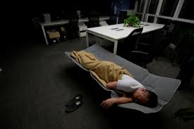 ma zhenguo a systems engineer at renren credit management co sleeps on a camp bed at the office after finishing work in the early morning camp bed office