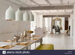 large white pendant lights hanging above an antique cherry wood dining table in open plan antique white pendant lighting