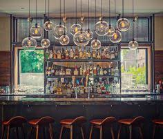 who would not want to have a drink here love the windows flanking the bar and of course the amazing lighting bar lighting design