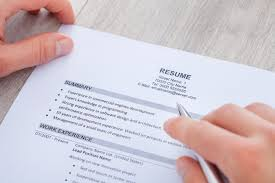 a businessman reads a resume on a table how to make a perfect resume step by step