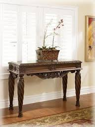 furniture t north shore: ashley north shore t  sofa table with  drawers scrolling accents and beveled top