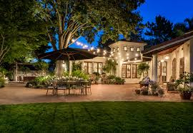 solar string lights outdoor with stone garden wall backyard string lighting ideas