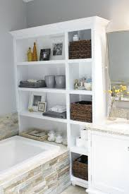 size bathroom wicker storage: wrought iron shelves with towels and rattan baskets over toilet storage