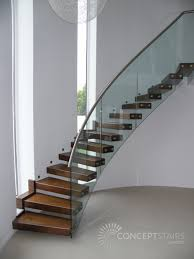 curved helical timber cantilever staircase with walnut treads curved glass balustrade supporting a stainless steel handrail and associated upper level bespoke glass staircase