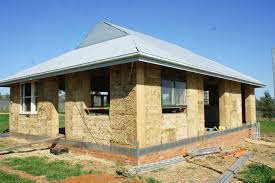 Latest technology in straw bale home construction comes to    A straw bale house under construction showing the bales and frame