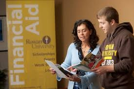 A Rowan financial aid counselor shows a male student information in a booklet