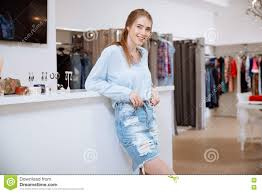 smiling attractive young w shop assistant stading in clothing smiling attractive young w shop assistant stading in clothing store