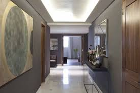 contemporary entrance hall lighting above metal framed wall mirror nearby modern silver vase across hallway bench bench lighting