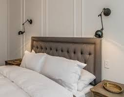 french bedroom features an accent wall adorned with decorative trim moldings lined with a gray linen tufted headboard on bed dressed in soft white bedding cb2 swing arm brass wall