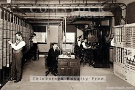 telephone office in early 19th century shows old telephone equipment two male operators sit at telephones man in center of photo talk on telephone century office equipment