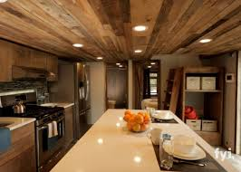 the spacious kitchen is capped by a ceiling consisting of paneling from reclaimed wood which gives the room a rustic vibe offset cleverly by sleek amazing rustic small home