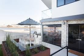 white striped patio umbrella: small water front patio features a stainless steel barbecue grill and a white dining table with a wood top surrounded by white modern dining chairs