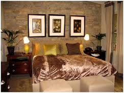 downights were used in this bedroom to accent art work and the texture of the stone wall a mix of table lamps were called upon to add task lighting as add task lighting