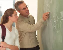 introduction teacher helping student at blackboard