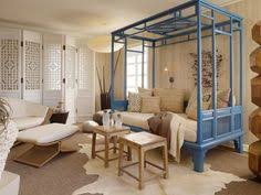 living room with bed: room of the day intriguing choices in this room with blue day bed screen animal hide rug and bench one room living