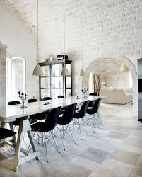 exposed limestone brick wall dining room with long farmhouse trestle table black eames chairs black white home office cococozy 5