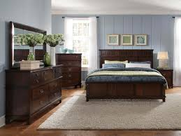 blue light walls bedroom with dark brown furniture set add cabinet with mirror also bed above bedroom with dark furniture