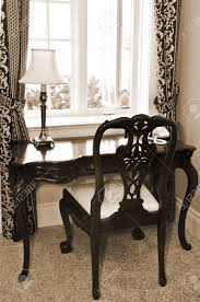 living room desks furniture: antique chair and desk near the window in living room stock photo