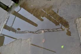 reflecting on auschwitz a photo essay words faspe a rain puddle reflection of auchwitz s infamous gate photo by valerie hopkins