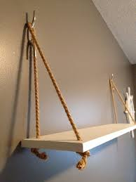 This is a nautical-themed hanging shelf made with painted wood ...