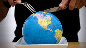 Knife and fork cutting into earth globe on a fast food plate
