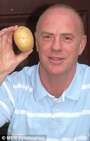 Richard Pickles with the potato in question, which was 'all burnt out' after the attempted quick fix - article-0-087647E4000005DC-429_233x363