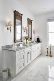 bathroom features gray shaker vanity: this traditional white master bathroom features white shaker style cabinetry with carrara marble countertops