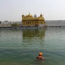 the golden temple tackk the golden temple is surrounded by a water tank that sikh practitioners use for cleansing rituals