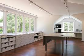 chic office features a series of track lighting illuminating a freestanding gray folding desks on wheels placed before built in shelves and drawers placed chic home office features